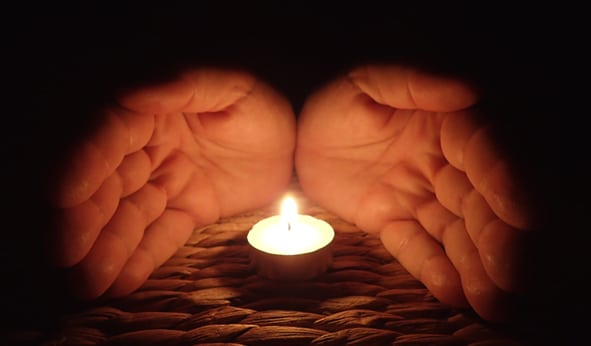 hands sheltering candle